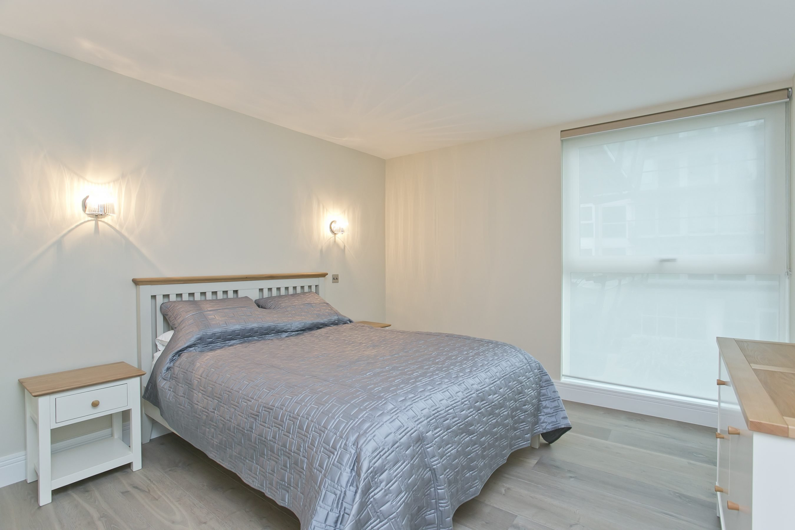 residential painting and decorating for light and spacious bedroom in Wapping, London: Walls in Dulux Almond White, woodwork and ceiling in Brilliant White