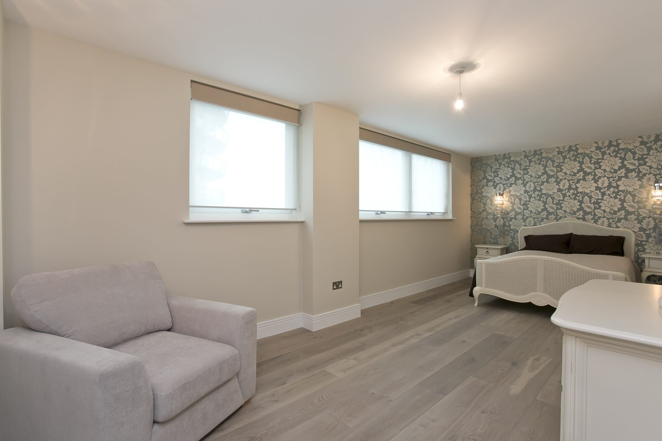 painting and decorating services for a spacious master bedroom with luxury floral wallpaper and Walls in Dulux Almond White, woodwork and ceiling in Brilliant White in Wapping, London