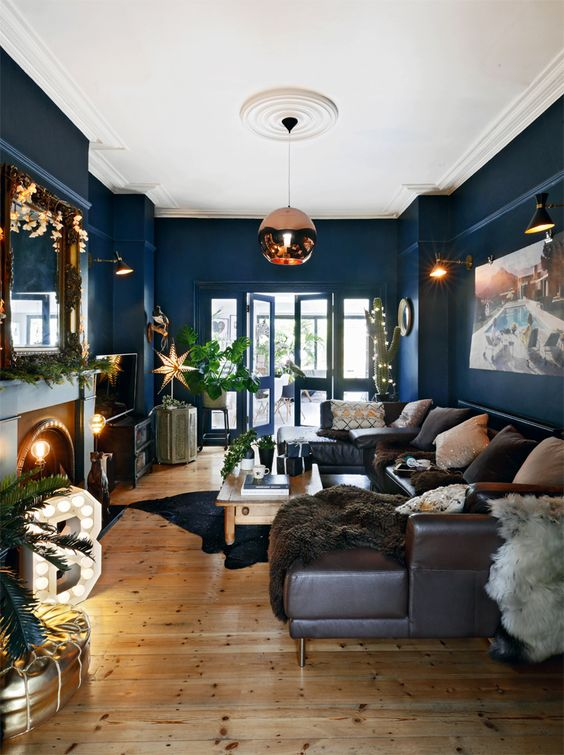 residential painting and decorating for living room with bright blue painted walls, white painted ceiling, wooden floor, large brown leather sofa, fire place and dreamy decor, London