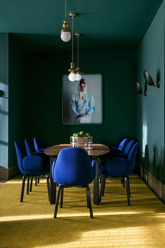 residential painting and decorating for bright dining room with yellow fcarpet, dark green walls and ceilings, wooden table and blue comfy armchairs, London