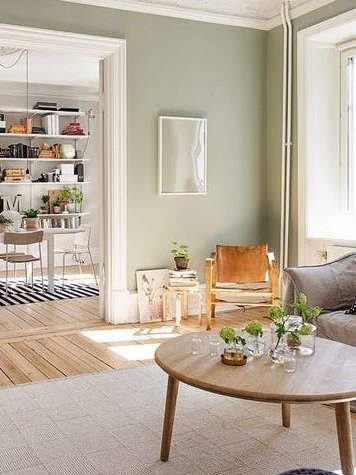 painting and decorating services for a spacious reception room with light green/sage painted walls, round wooden coffee table