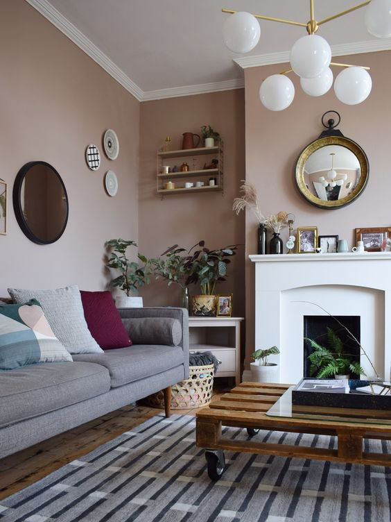 painting and decorating services for spacious reception room with peach painted walls, white fireplace, wooden pallet coffee table on rollers, light blue sofa and beautiful home decor