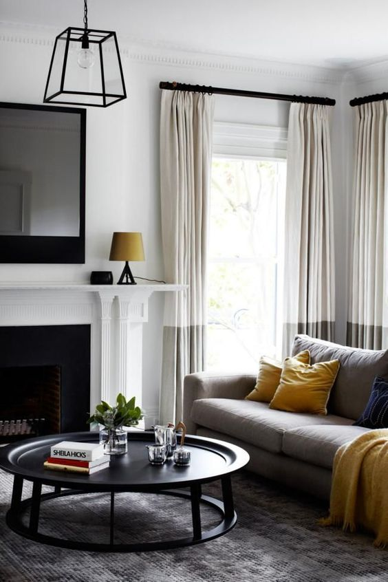 painting and decorating services for spacious living room withwallsa nd ceiling painted white, black, round, wooden coffee table, comfy grey sofa, black and white fireplace, London