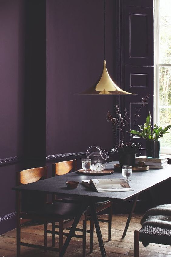 residential painting and decorating services for luxury dark dining room wih walls painted dark purple, black wooden furniture, and dark purple door