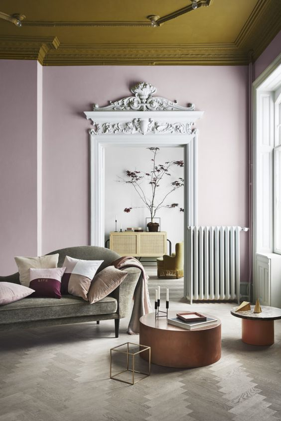 residential painting and decorating for spacious modern living room with mustard painted ceiling, pink painted walls, round coffee tables and light grey designers sofa, London