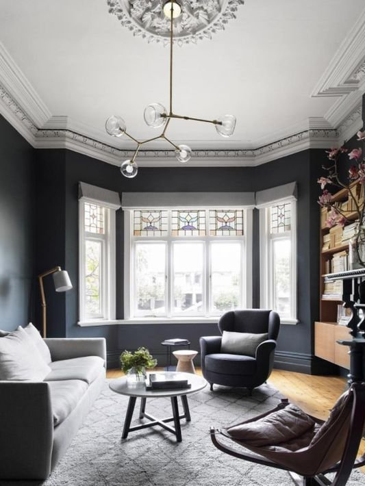 grand and spacious interior design for living room with dark navi painted walls, large bay window, comfy blue armchairs, light sofa