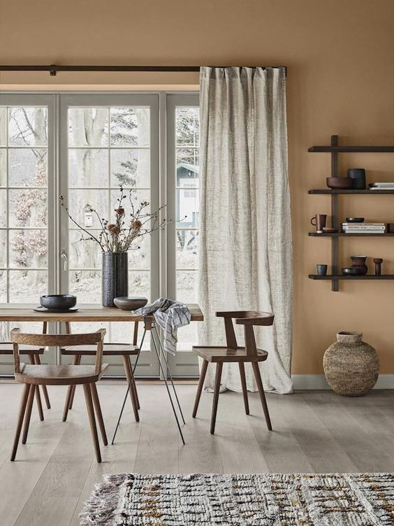 painting and decorating services for a dining room in scandinavial interior stylewith warm neutral painted walls, wooden dining table and chairs and large glass doors