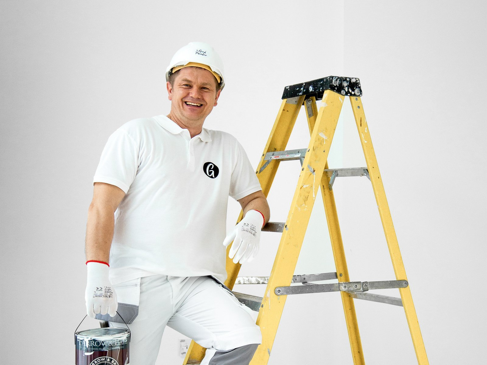Painter and decorator Marcin with Farrow and Ball painting on the ladder, London