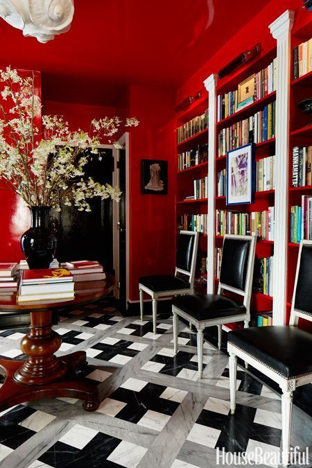 bright and playful interior design for home library with red painter walls and ceiling, black and white tiled flooring, and black chairs