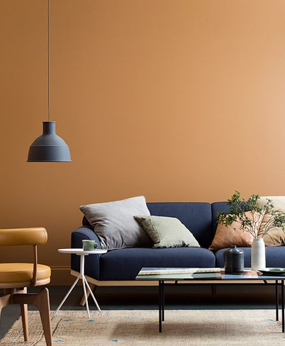 playful interior for a living room in scandinavian style with warm warm painted walls and blue sofa