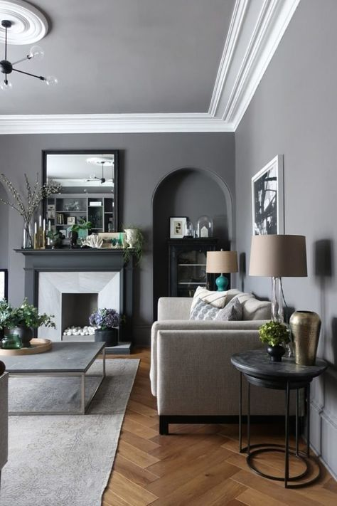 residential painting and decorating services for spacious living room painted dark grey with fireplace, light comry sofa and square glass coffee table