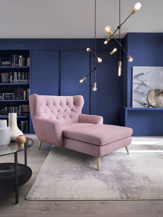playful colourful interior with dark navi walls, comfy pink armchair