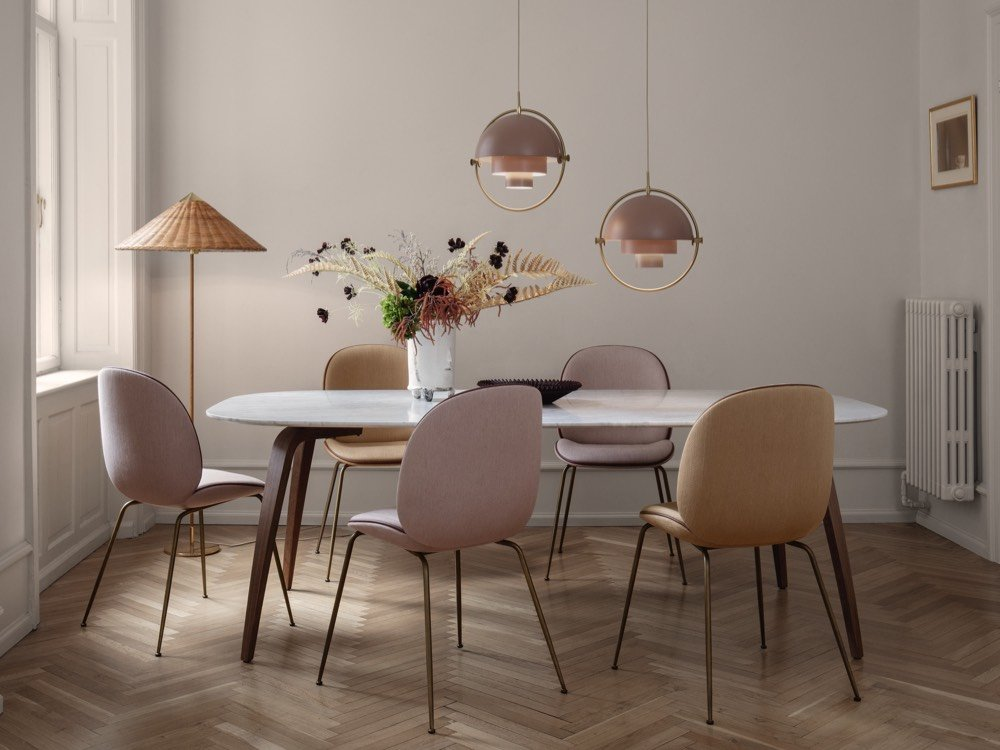 light and spacious dining room with neutral painted walls, light table, pinky chairs and lightings
