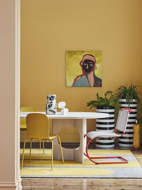 playful interior design for spacious dining room with yellow painted walls, wooden table, yellow chairs and grey and yellow carpet